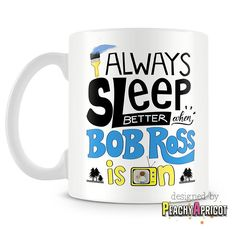 "The Bob Ross Mug is our brand new creation inspired by the soft, relaxing and soothing voice of Bob Ross. Relax and experience Bob Ross's calm happiness with this unique ""I sleep better when Bob Ross"