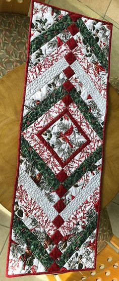 Five different coordination Christmas Cardinals fabrics make up this beautiful table runner which can also be used as a wall hanging or bed runner for the Holidays and even into the new year. The chevron style is classy and will look fantastic with Christmas dinnerware in White, Table Runner And Placemats, Table Runner Pattern, Quilt Table Runners, Patchwork Table Runner, Christmas Runner, Christmas Table Runners, Christmas Quilting, Christmas Sewing, Skinny Quilts