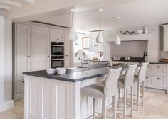 Lloyd Loom barstools sit at a stylish island unit with grey limestone and textured granite worktops in this bespoke shaker kitchen by Cheshire Furniture Company.