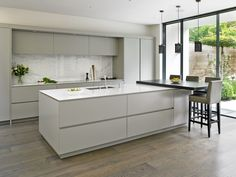 Wandsworth Family Kitchen – Bespoke Kitchens, SW London Sleek handleless kitchen design with large island & breakfast bar, marble splashback and floor to ceiling sliding doors leading out into the garden. Handleless Kitchen, Luxury Kitchens, Kitchen Remodel, Contemporary Kitchen, Kitchen Layout, Modern Kitchen Design, Minimalist Kitchen, Kitchen Living, Kitchen Design