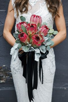 protea bouquet with ribbons - photo by Boyfriend Girlfriend http://ruffledblog.com/elegant-toronto-wedding-inspired-by-dolce-and-gabbana #bouquets #weddingbouquet #flowers