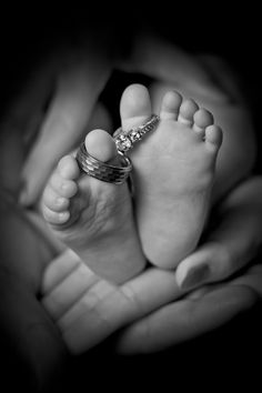 Newborn baby wedding rings on toes cupped in mothers hands