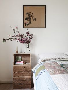 vintage style bedroom with beautiful art, flowering branches, quilt and stacked recycled crates as night table -  Tamsin Carvan and Family — The Design Files