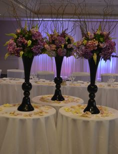 Tall purple floral arrangements in black vases. Styled by Greenstone Events.