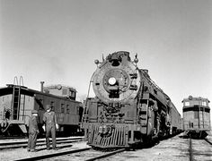 Santa Fe crewmen chat before departing Vaughn, New Mexico with an eastbound train, led by 2-10-4 #5006, during March of 1943. The AT&SF's Texas fleet were all products of Baldwin with #5006 being outshopped in 1938. Jack Delano photo.