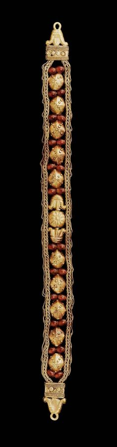 Carnelian and Gold Bracelet. Nubian, Meroitic Period, 1st century B.C. Nubia, Sudan. Braided gold wire bracelet. Between the two strands, a gold rosette in the center with a gold lotus flower on each side and gold ornaments alternating with carnelian beads. On each end a lotus flower terminating in a loop fastener.