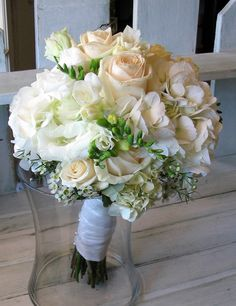 Bridal bouquet with ivory roses, white hydrangea, and white freesia buds