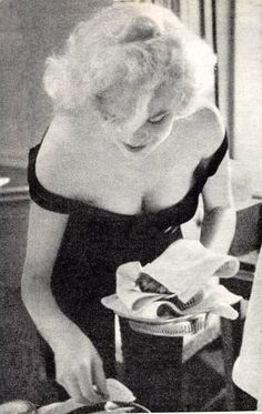Marilyn clearing plates after a dinner with Arthur, Yves Montand and Simone Signoret in the Montand's hotel room during the filming of 'Let's Make Love', 1960. Photo by Bruce Davidson.