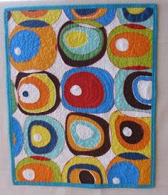 Colorful circles quilted wall hanging.  Lots of free motion quilting on an Alexander Henry fat quarter