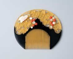 Celluloid kushi with cutwork depicting leaves with coral- and white-colored buds. - MIHO MUSEUM