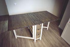 Decoración y acabado en mesa plegable de pino.  Teñido y barnizado a muñequilla sobre tapa de madera de pino. Pintura blanco tiza en patas....