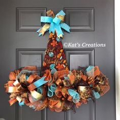 This is my new design for Fall!!! This gorgeous Fall Thankful Hat Wreath!! From the blues, oranges, and browns, this needs no sign as the word Thankful is displayed with the fabric. Measuring 24-inches wide and 24-inches long, and a full 5.5 inches thick, this is perfect for someone wanting something truly unique. Created from formed cotton fabric, this mixes a variety of elements to create just the right look. It features metallic deco mesh, 8 different ribbons, metallic ball…