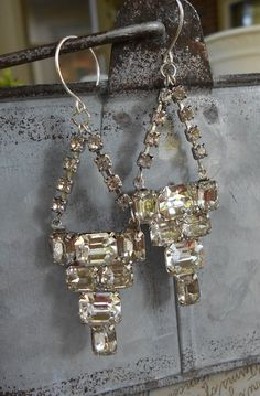 Art Deco rhinestone assemblage earrings brilliant stones dress clips one-of-a-kind glam Triolette  Slip these rhinestone statements on and instantly feel glamorous! The main components of these assemblage earrings are geometric rhinestone dress clips with a total of 14 large cushion cut stones. The stones are prong set and sparkle relentlessly. They connect to the silver curved ear wires with vintage rhinestone cup chain. Although they have a large striking presence, these earrings are equal…