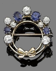 A sapphire and diamond brooch, circa 1900.  Modelled as a wreath decorated by a bow, set with oval and circular-cut sapphires, and cushion-shaped diamonds, diamonds approx. 2.35cts total, diameter 2.8cm