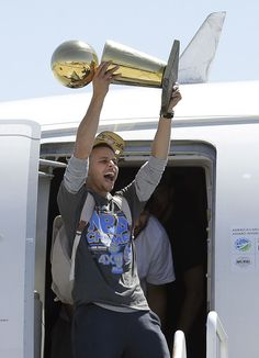 Golden State Warriors guard Stephen Curry yells as he lifts the Larry O'Brien championship trophy after the team landed in Oakland, Calif., June 17, 2015. <span class=meta>AP Photo/Jeff Chiu</span>