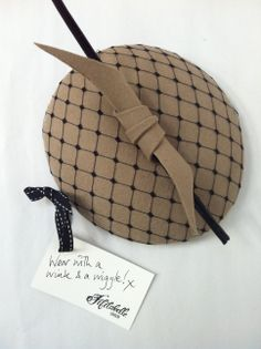 A hand made bespoke cocktail hat - beige and black, netted, with a huge feather quill! www.fifilabelle.com