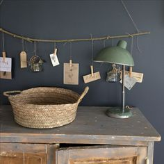 Old wooden dresser | Green lamp | Basket | Dark wall | Twig branch and suspended cards | Display home
