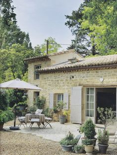 Rustic French country home with stone exterior, light gray shutters and a pea gravel patio with potted plants and bistro-style patio furniture.