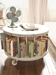 awesome! round coffee table/book shelf made from a wooden cable spool. all you need is a comfy couch and cuddly blanket. oh and fresh coffee. mmm. best wake up ever.