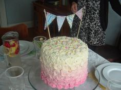 Ombre bunting cake. Swirl icing into a layer cake using a flower piping nozzle. Start with white and slowly add more colour as you pipe down your cake. Use pastel scrap paper to create bunting to spell out the name of the birthday boy or girl and attach to cake with wooden kebab sticks