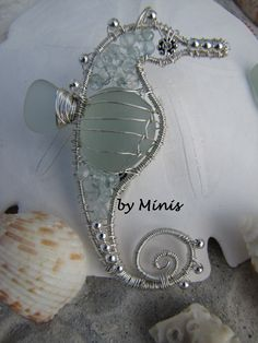 Sea glass, sterling silver wire , sea horse pendant. I used sea glass, 26 gauge sterling silver wire over 18 gauge wire, 3 mm sterling silver round beads, 5 mm sterling silver daisy bead for the eye, faceted aquamarine beads.
