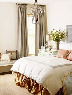 A subdued palette of neutrals with gray, bronze, and green keeps this master bedroom peaceful. Barely-there dove gray covers the walls, while stone gray adds depth in the curtain panels and on the headboard. A slim border of gray embellishes the white bedding. A small-scale chest of drawers in soft green serves as a nightstand. Warm hues come from a bronze bedskirt and coral-pattern pillows.