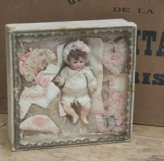 5 1/2 (14 cm.) doll. 8 x 8 x 2 1/2 box. A glass-fronted box with decorative paper gilt edging displays a bisque-head doll with pink-tinted bisque