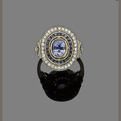 A sapphire and diamond cluster ring  The collet-set oval-cut sapphire within a calibré-cut sapphire border, to a further brilliant-cut diamond surround, between similarly-cut sapphire and diamond shoulders, diamonds approx. 0.40ct total, ring size N, cased by M. Kemp, Nottingham; done in a neo-classic style.