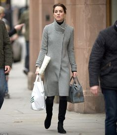 Elegant: The mother-of-two added a touch of colour with a muted blue bag, as she carried her John Lewis plastic bag in the other hand