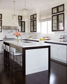 Black and white kitchen-- love the mix of black cabinet frames + glass & White square style cabinets