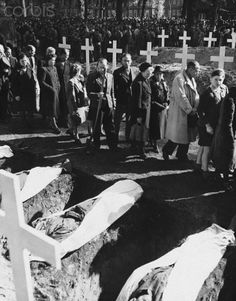 German civilians of Ludwigsluts, Germany, file past the graves of the 200 victims of starvation and torture in the Nazi concentration camp near Wobbelin, Germany. The bodies were brought here for burial by German civilians under the supervision of soldiers of the 82nd airborne division.