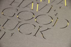 laser cute type...there might be a layer of metallic gold paper underneath or gold leaf?