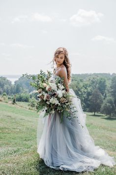 Beautiful oversized bridal bouquet and an exquisite gray wedding dress.