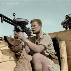 """A member of a Long Range Desert Group patrol poses with a Vickers """"K"""" gas-operated machine gun on a Chevrolet 30-cwt truck. (May 1942). Colorized by Retropotamus."""