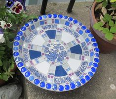 A blue and white mosaic birdbath, with materials including a willow pattern china plate, glitter tiles and glass pebbles. Mosaic Birdbath, Mosaic Garden, Mosaic Glass, Pedestal, Glitter Tiles, Shop Signage, Diy Bird Bath, Mosaic Birds, Rainbow Glass