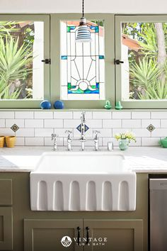 The vintage stained glass panel, green cabinets, and fluted fireclay farm sink add a statement to this lovely farmhouse kitchen.