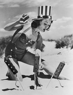 Actress Louise Synder wears a vintage swimsuit and a Stars & Stripes top hat to set off fireworks for a Fourth of July celebration on the beach in 1950.