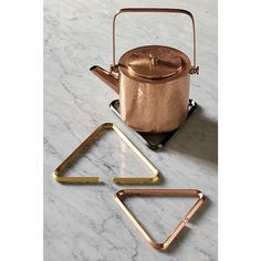 Shop 3-piece range metal trivet set.   Trio of iron triangular trivets take a steaming seat at the table.  Glam rose gold, silver and brass bent metal rods triangulate the perfect lift for hot plates and platters.