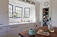 Gorgeous kitchen features light grey shaker cabinets adorned with brass hardware topped with white marble fitted with a white porcelain sink and brass gooseneck faucet under a bay window.