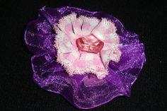 flor confeccionada en lazo de organza lila y gasa de cuadros rosa-blanco, en el centro detalle de botón de cristal rosa