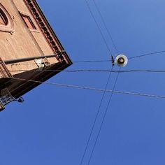 Da fare a Bologna: guardare in su quando è bel tempo perché poi è un attimo che viene a piovere o viene caldo e ci si scorda che il cielo è effettivamente blu dietro lo smog. E poi guarda quanti fili intrecciati e che bel lampione vintage.  Piazza Santo Stefano Bologna.