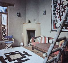 1. The wood ladder gives this nature feeling. 2. Rug and the thing on the wall give this room a native/spanish look. 3. The whole room is filled with soft neutral colors from the rug to the wall.