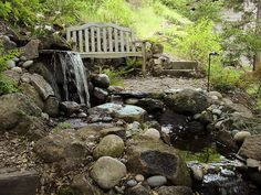 Natural Backyard Escape: River rock water feature, flagstone and teak bench.