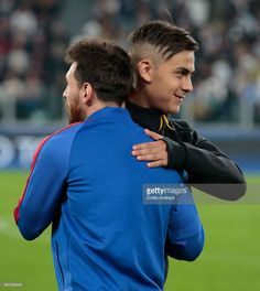 Paulo Dybala of Juventus FC embraces Lionel Messi of FC Barcelona during the UEFA Champions League Quarter Final first leg match between Juventus and FC Barcelona at Juventus Stadium on April 11, 2017 in Turin, Italy.