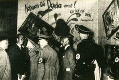 """Adolf Hitler visiting the """"Dada Wall"""" in the Entartete Kunst Exhibition. The exhibit was designed as a horror show of modern art, which the Nazis believed was unhealthy because non-representational, abstract, and cosmopolitan. The pictures, including paintings by Marc Chagall, Otto Dix, Georg Grosz, Wassily Kandinsky, and Paul Klee, were hung to produce a chaotic, dizzying effect."""