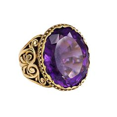 Antique Amethyst Gold Ring. An antique gold and amethyst ring, The cushion-shaped amethyst set in a pierced mount with shoulders of open scrollwork, in 18k. C 1880