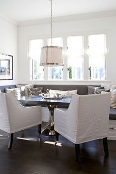 Love the silver metal chrome white pendant lighting, wood dining room table, gray upholstered bench, built-in banquette, slip-covered dining chairs and white paint wall color! Love the pretty white roman shades on the windows! Love the espresso wood floor Kitchen Banquette, Banquette Seating, Dining Nook, Kitchen Nook, Kitchen Seating, Crisp Kitchen, Kitchen Booths, Kitchen Grey, Dining Tables