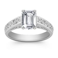 6.9mm x 4.8mm Emerald cut White Sapphire  This stylish and distinctive vintage inspired design highlights intricate side engraving with milgrain detailing. Eight round diamonds at approximately .04 carat total weight, are bezel-set in an exquisite 14 karat white gold setting. This elegant design awaits the center diamond of your choice. Shown with a center stone Emerald Cut White Sapphire.