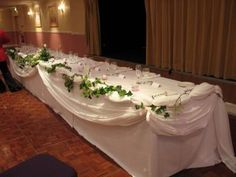 ivy dedorated chairs | Top table decoration with swagged white muslin and fresh ivy.