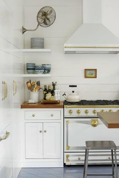 Channeled the Past The Brocks wanted their kitchen to look as if it had been added on in the early 20th century. That meant shiplap walls, no upper cabinets, mahogany countertops, and unlacquered brass hardware. They either hid appliances, such as the refrigerator, or chose versions that had a vintage vibe. With its creamy finish and brass accents, you would think at first glance that the range was from decades ago.